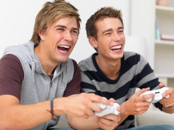 Closeup of two friends playing video game