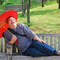 mężczyzna park ławka śmiech parasolka